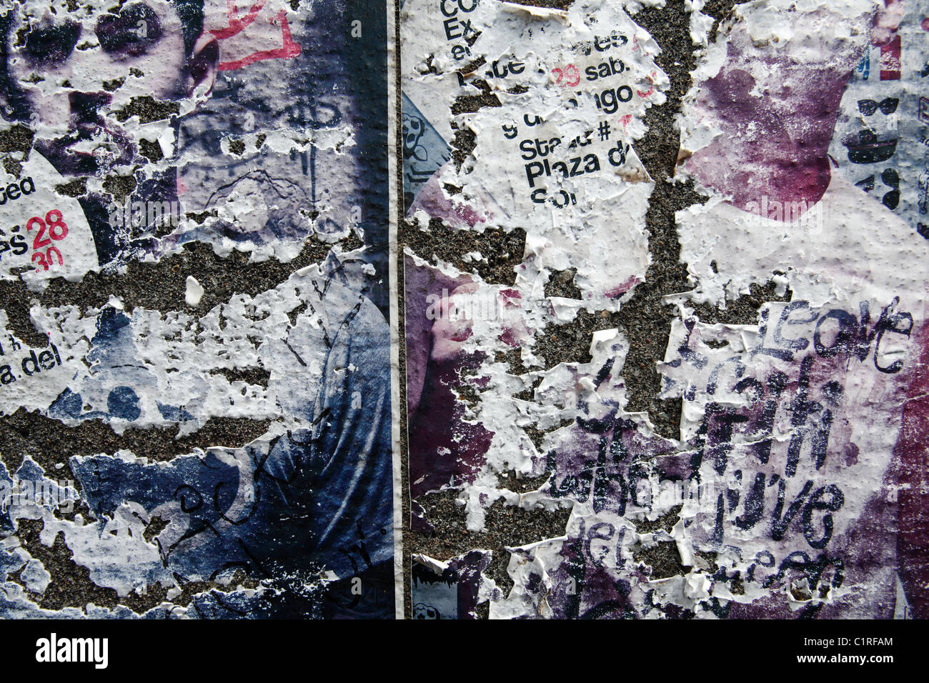 remnants of posters on a wall - Stock Image