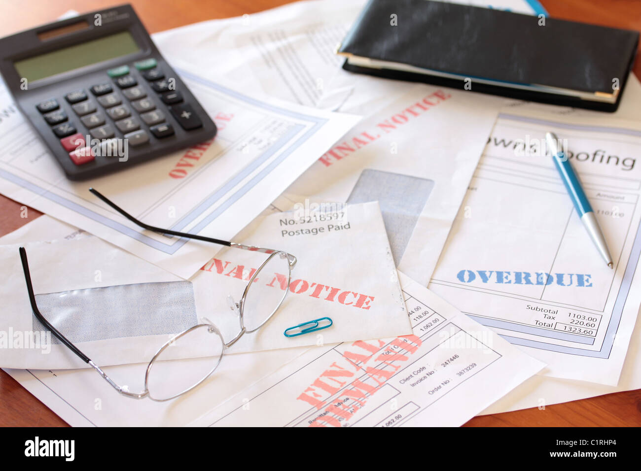 'Overdue Unpaid Bills on Table with Calculator and Cheque Book ' - Stock Image