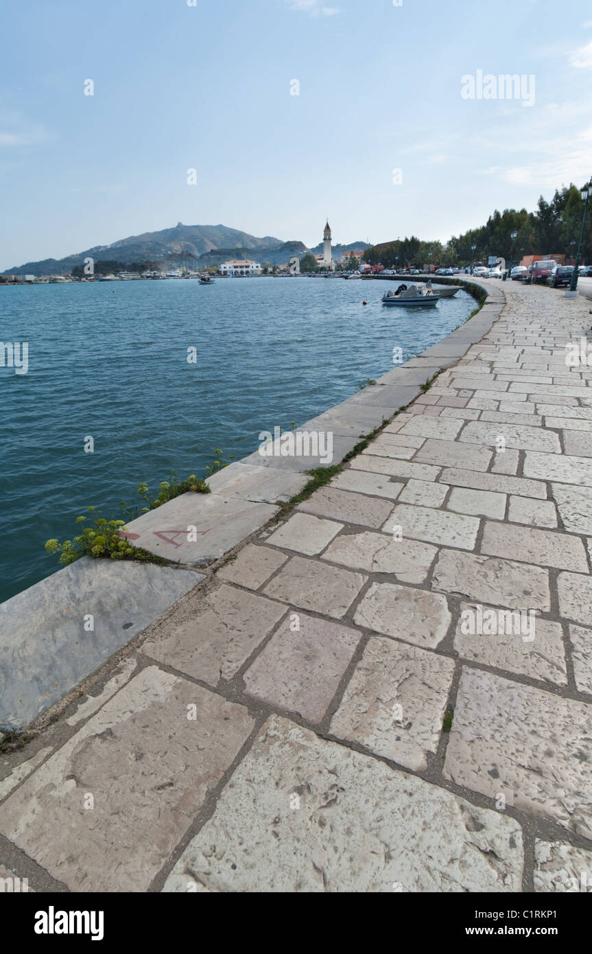 This stone sidewalk surrounds the busy harbour in the town of Zante on the island Zakynthos in Greece. - Stock Image