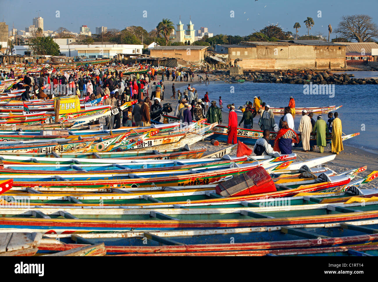 Colorfully painted fishing boats line the beach at the fish market in Dakar, Senegal - Stock Image