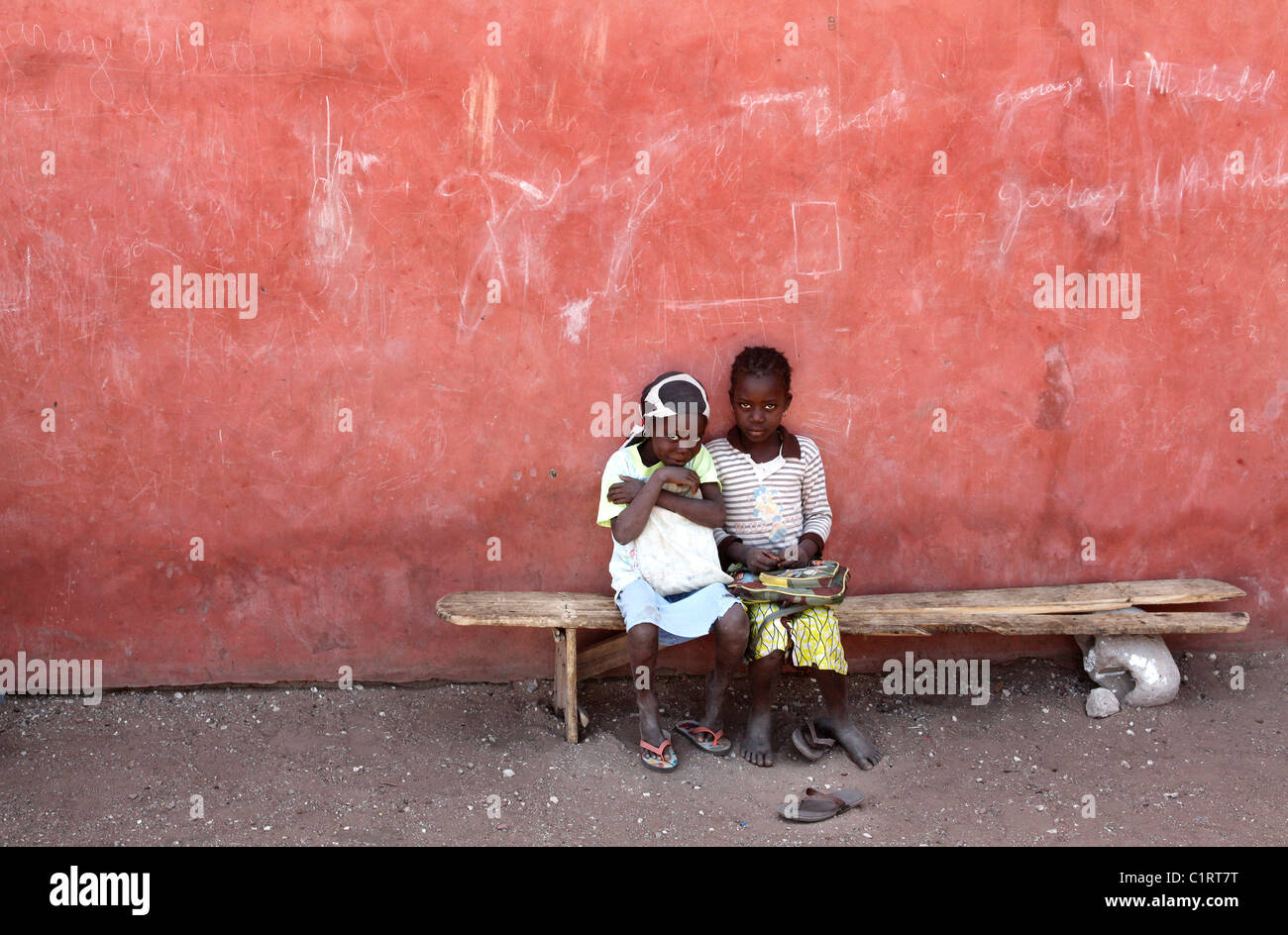 two shy girls sitting on a wooden bench, Senegal, Afrika - Stock Image