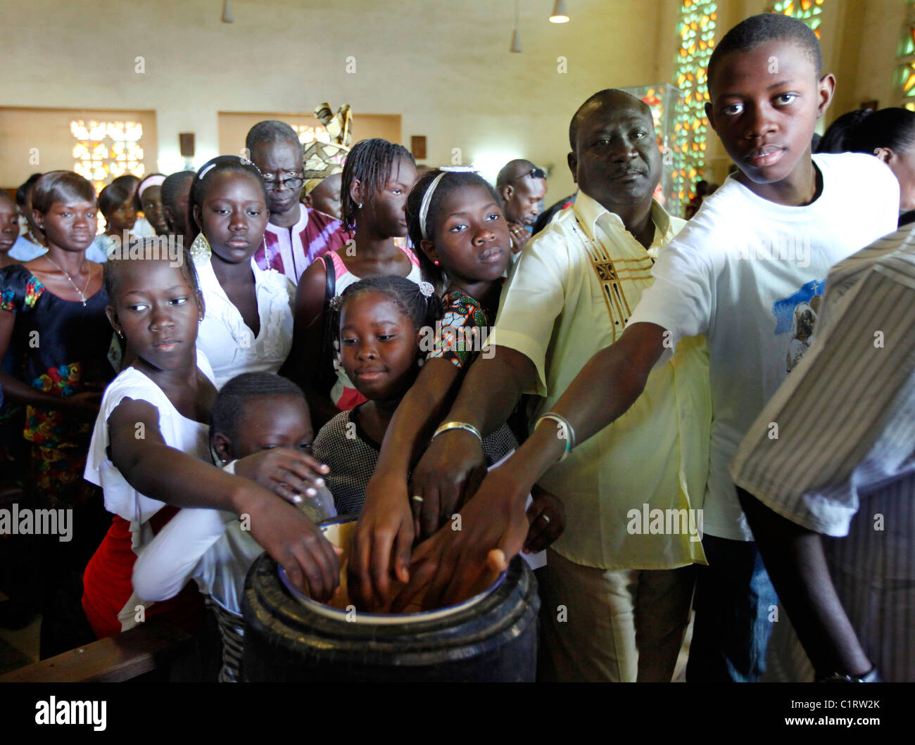 Senegal: Sunday mass at a Roman Catholic church in Kaolack, worshippers at the holy water stoup - Stock Image