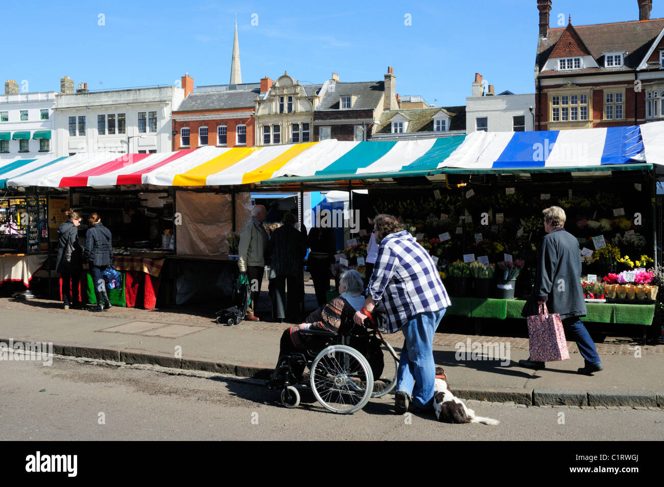 Stalls on the Market, and Man pushing Senior Woman in Wheelchair, Cambridge, England, UK - Stock Image