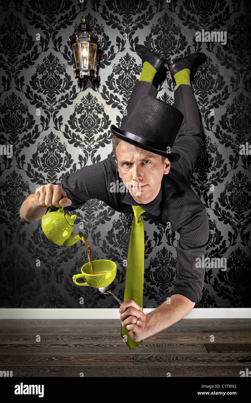 A levitating magician is pouring tea in a cup balanced on a spoon. - Stock Image