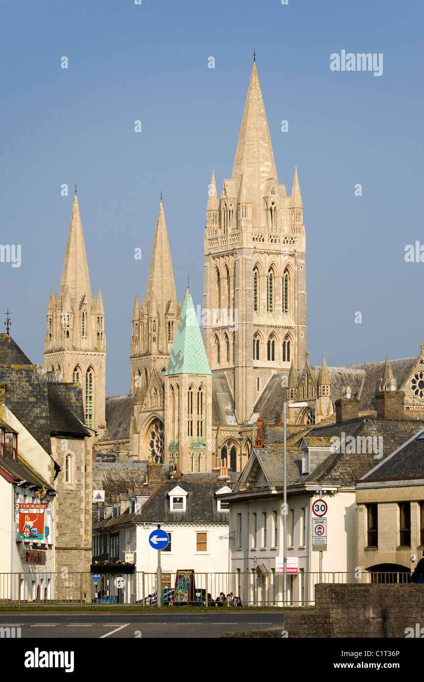 The three spires of Truro cathedral tower above buildings in the Cornish city centre against a blue sky - Stock Image