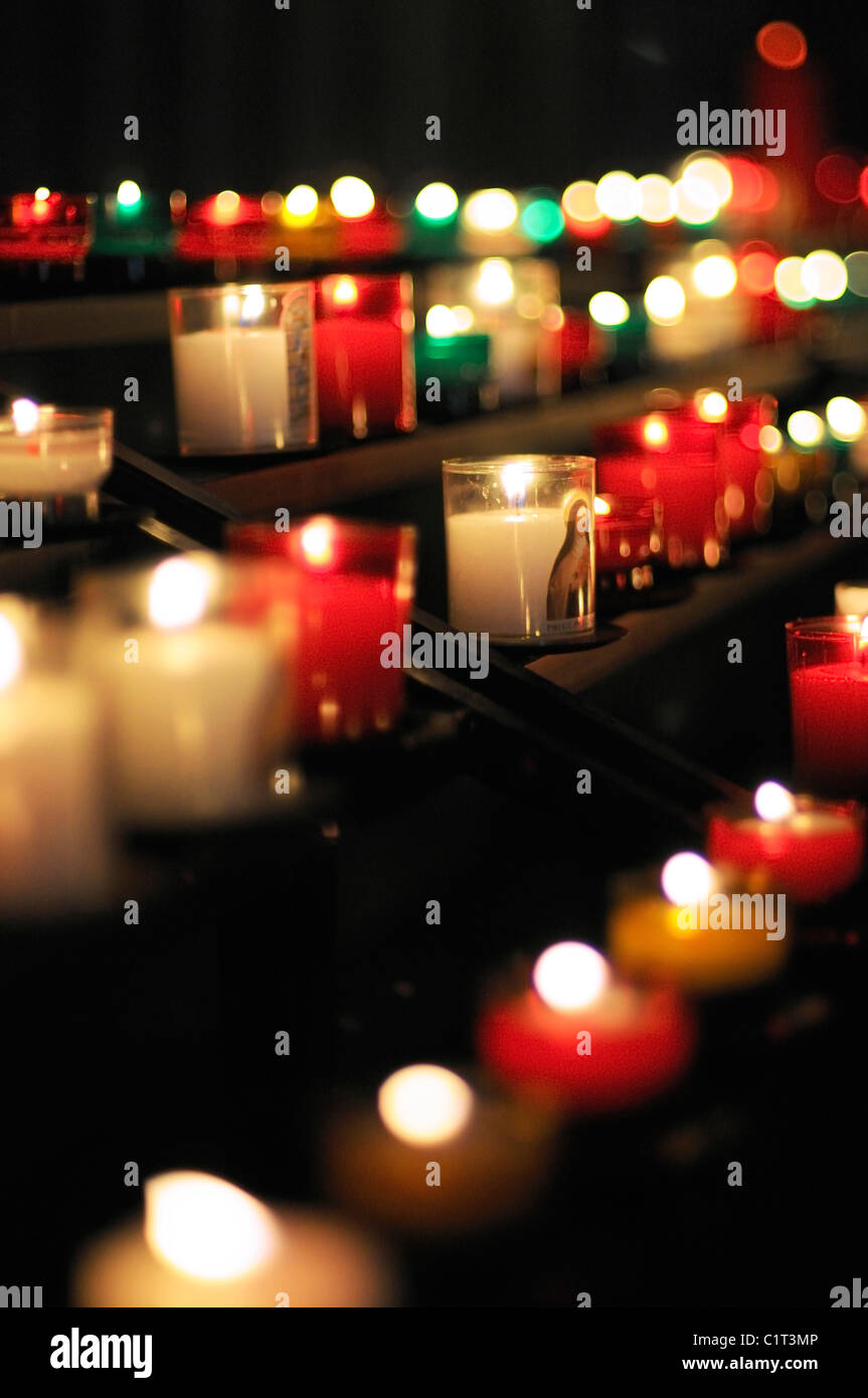 Votive candles burning in church - Stock Image