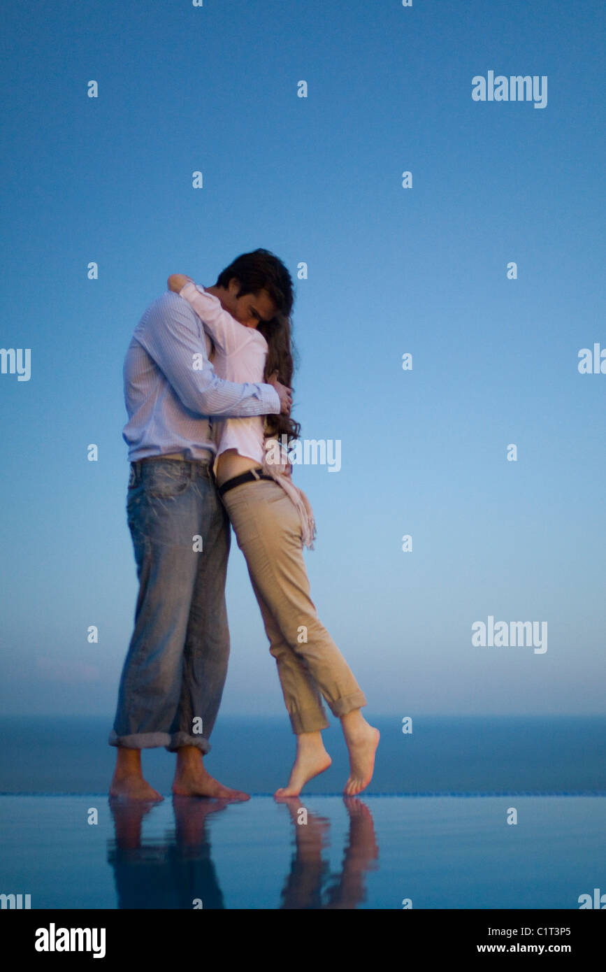 Couple embracing on edge of infinity pool at dusk - Stock Image
