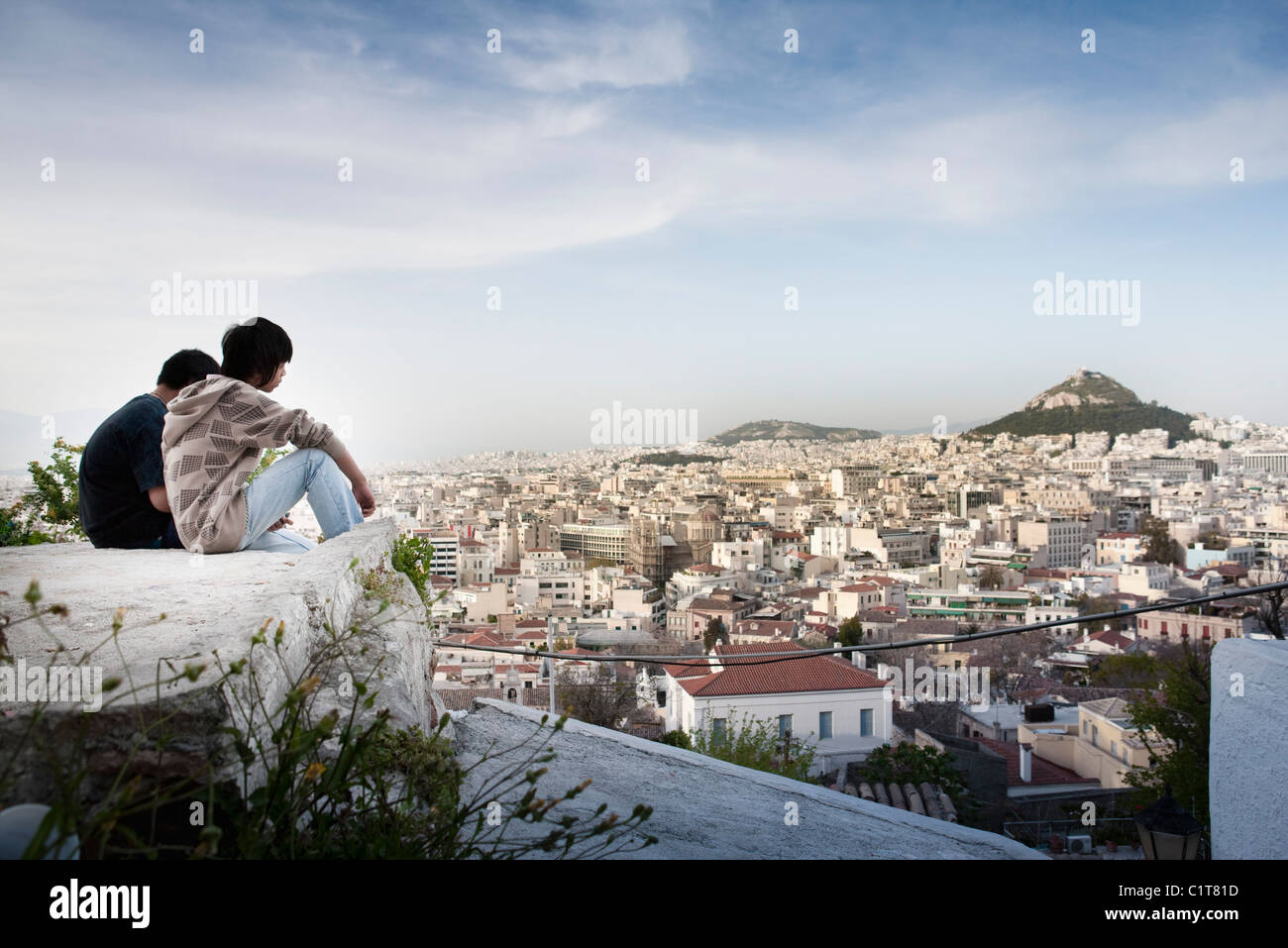 Tourists sitting on rock overlooking Athens, Greece and Mount Lycabettus - Stock Image