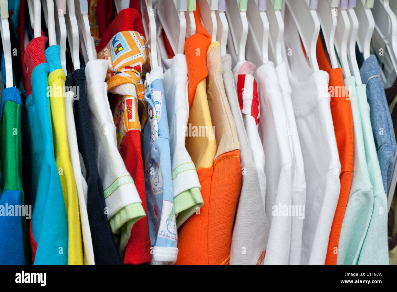 Shelving with varicoloured cloth on plastic hatrack - Stock Image