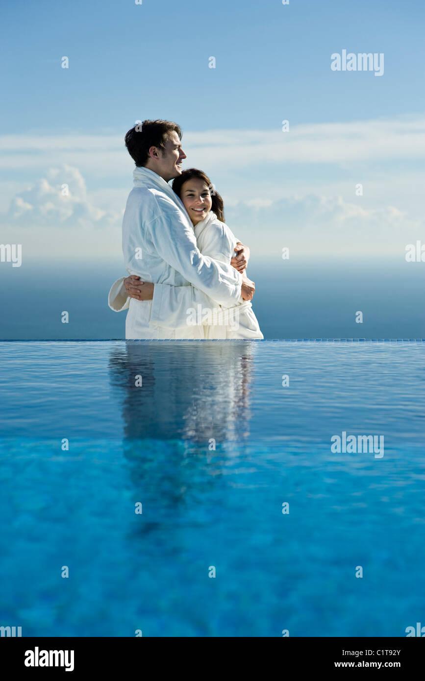 Couple embracing at edge of infinity pool, both wearing bathrobes - Stock Image