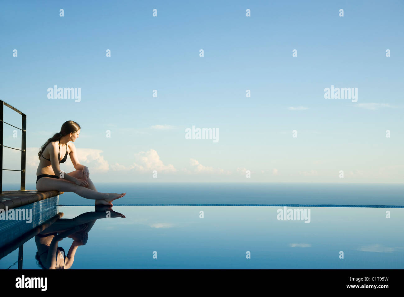 Woman sitting at edge of infinity pool, looking at view - Stock Image