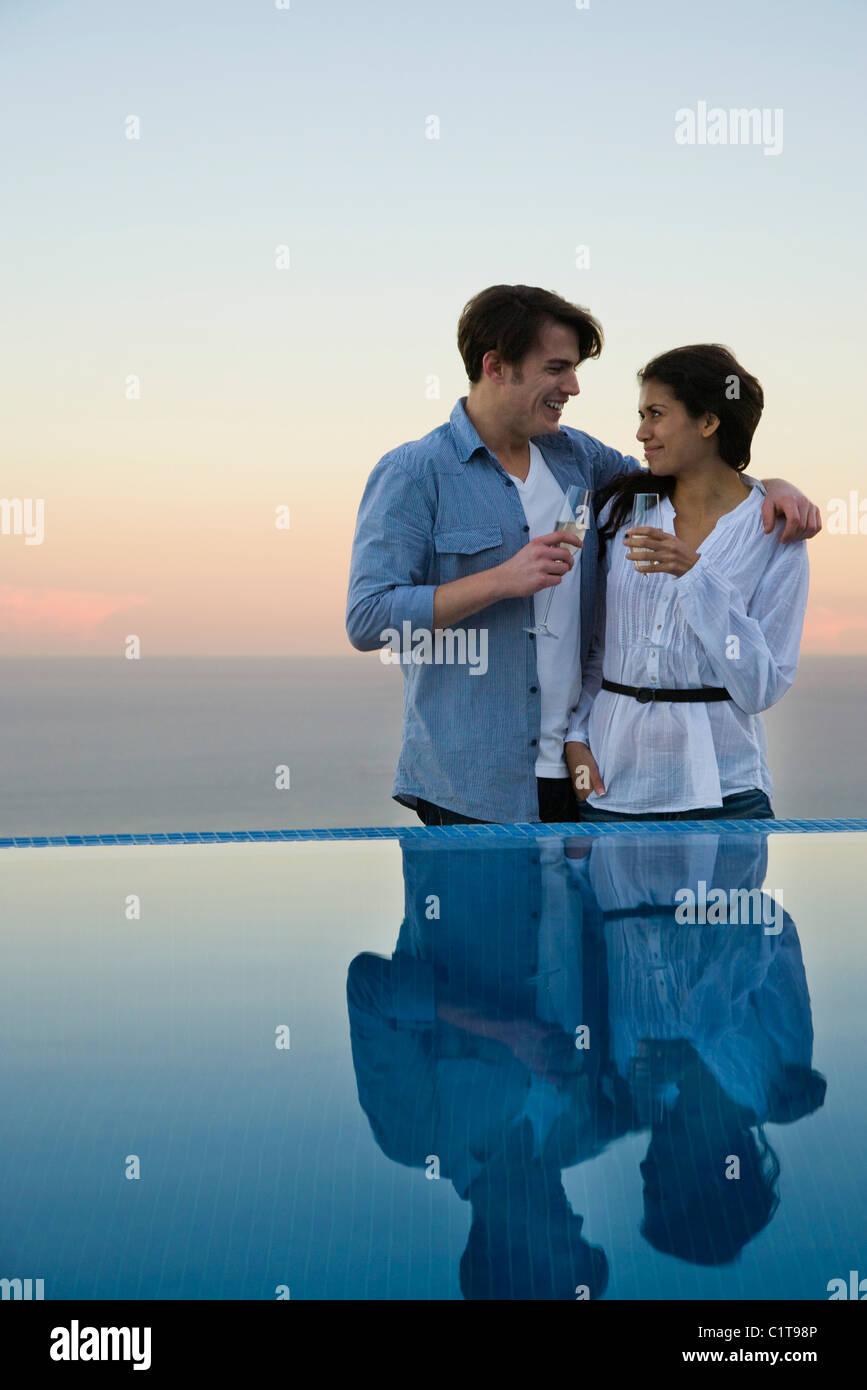 Couple standing at edge of infinity pool, enjoying champagne - Stock Image