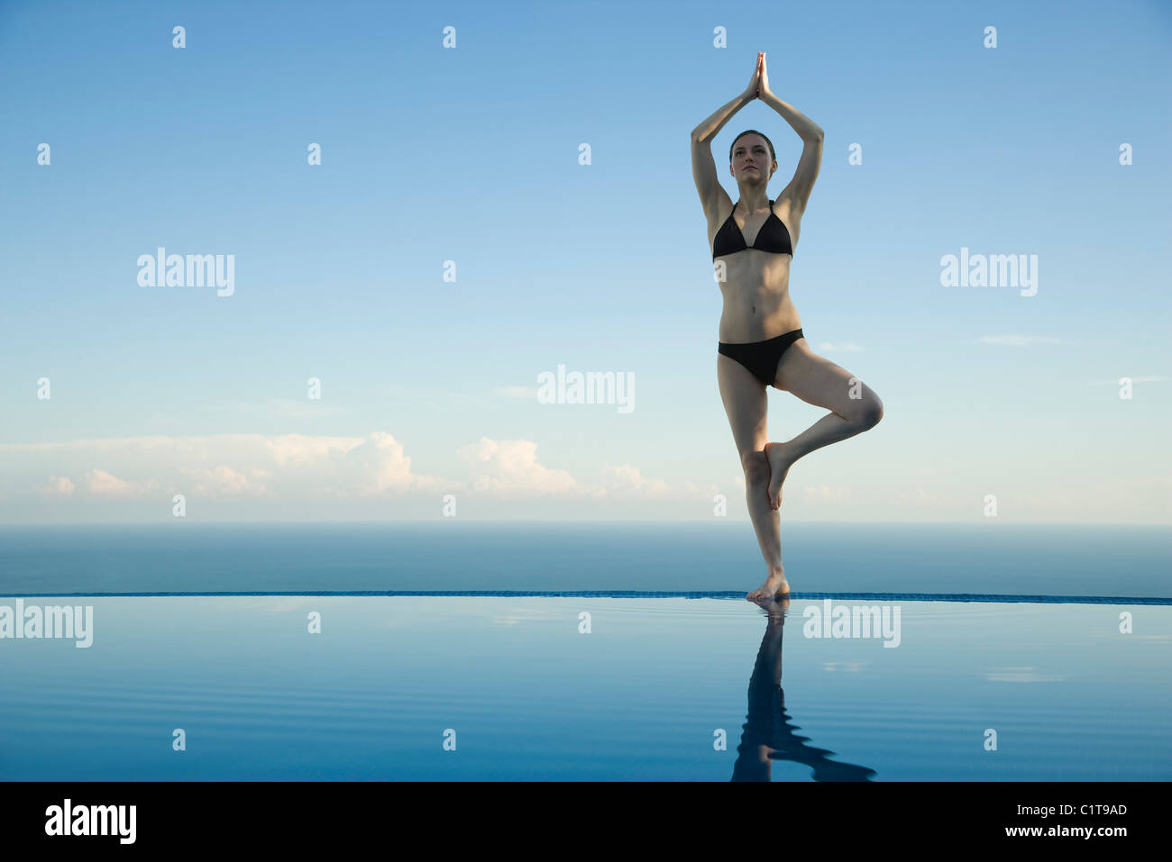 Woman standing in tree pose on edge of infinity pool - Stock Image