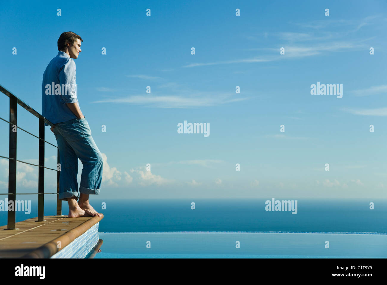 Man standing at edge of infinity pool, looking at view - Stock Image