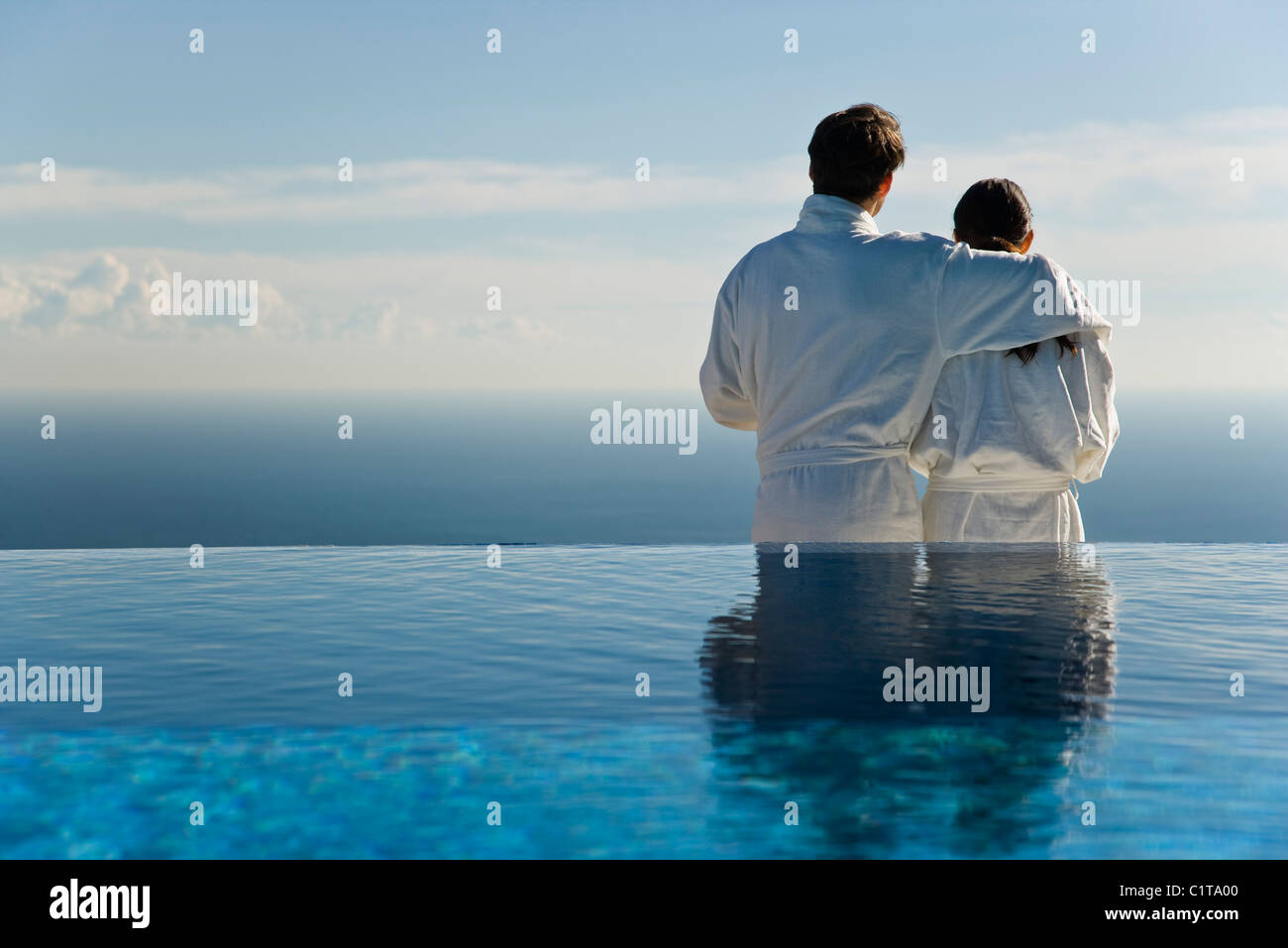 Couple standing at edge of infinity pool, looking at view - Stock Image