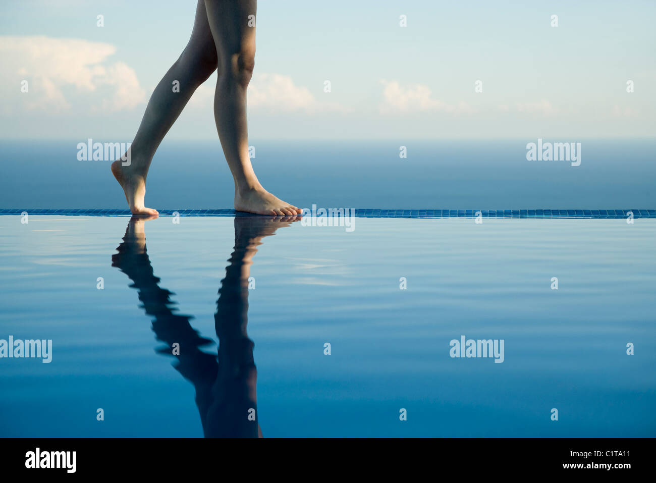 Woman walking along edge of infinity pool, low section - Stock Image