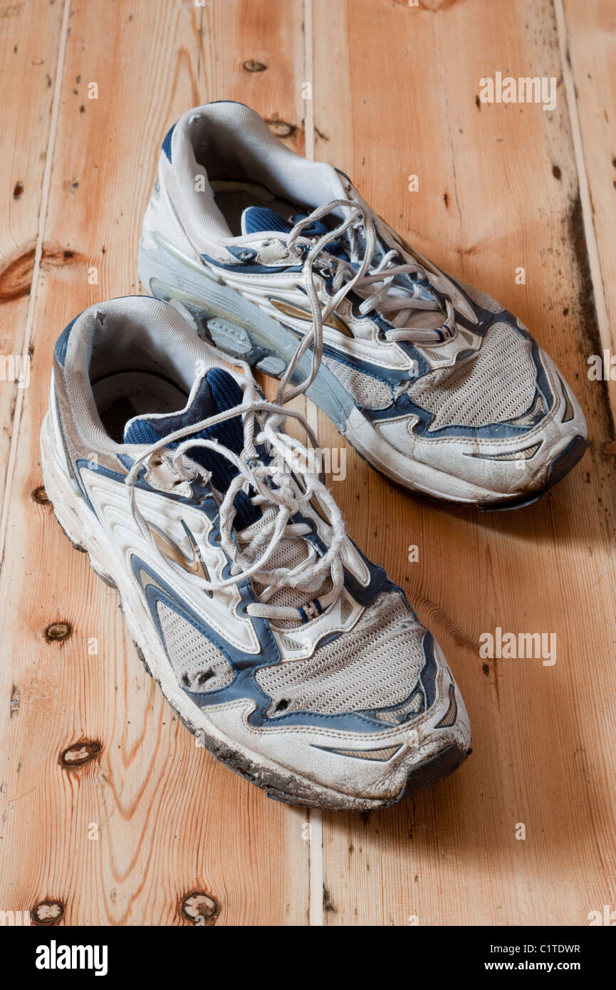 Old pair of tired and worn out training or running shoes. - Stock Image