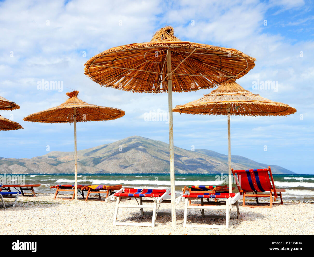 deserted beach couches and straw parasols ready for customers on a summer day on the adriatic coast of Albania - Stock Image