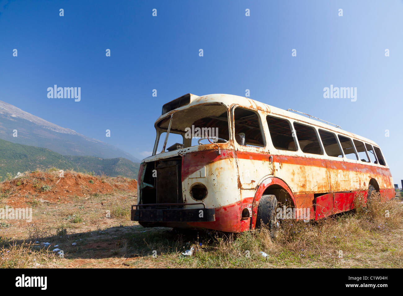 stripped rusty, old abandoned red bus wreck in arid mountainous landscape of Montenegro - Stock Image