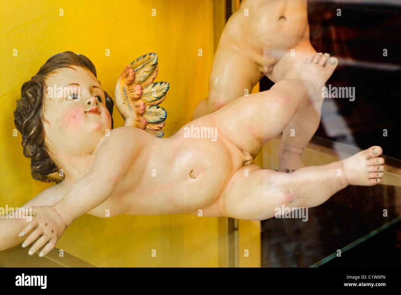 Statue of cherub in antique shop window, Marbella, Spain. - Stock Image