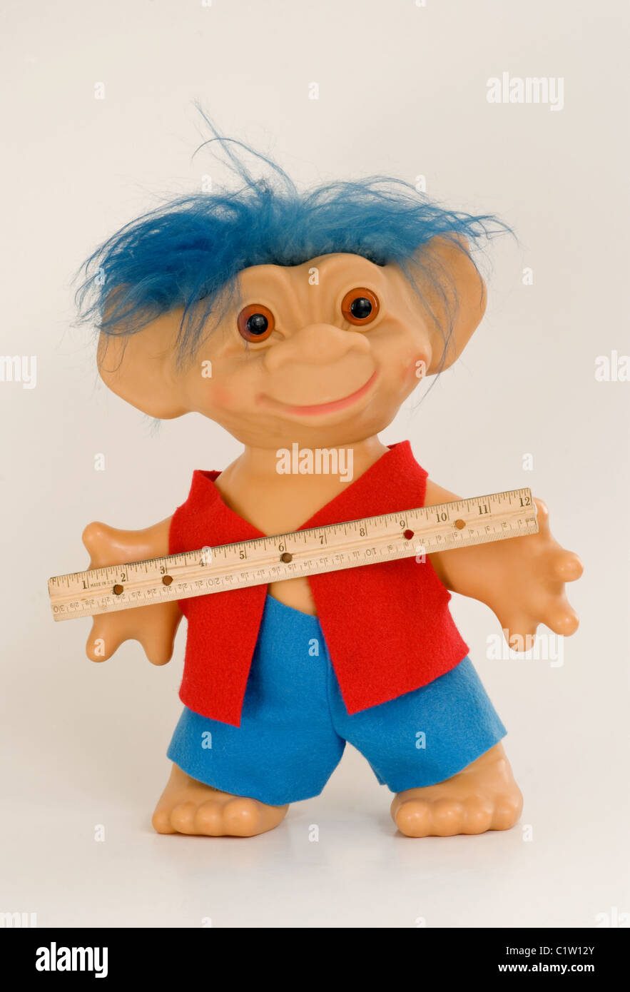 Troll boy with blue hair holding a ruler with inches and centimeters - Stock Image