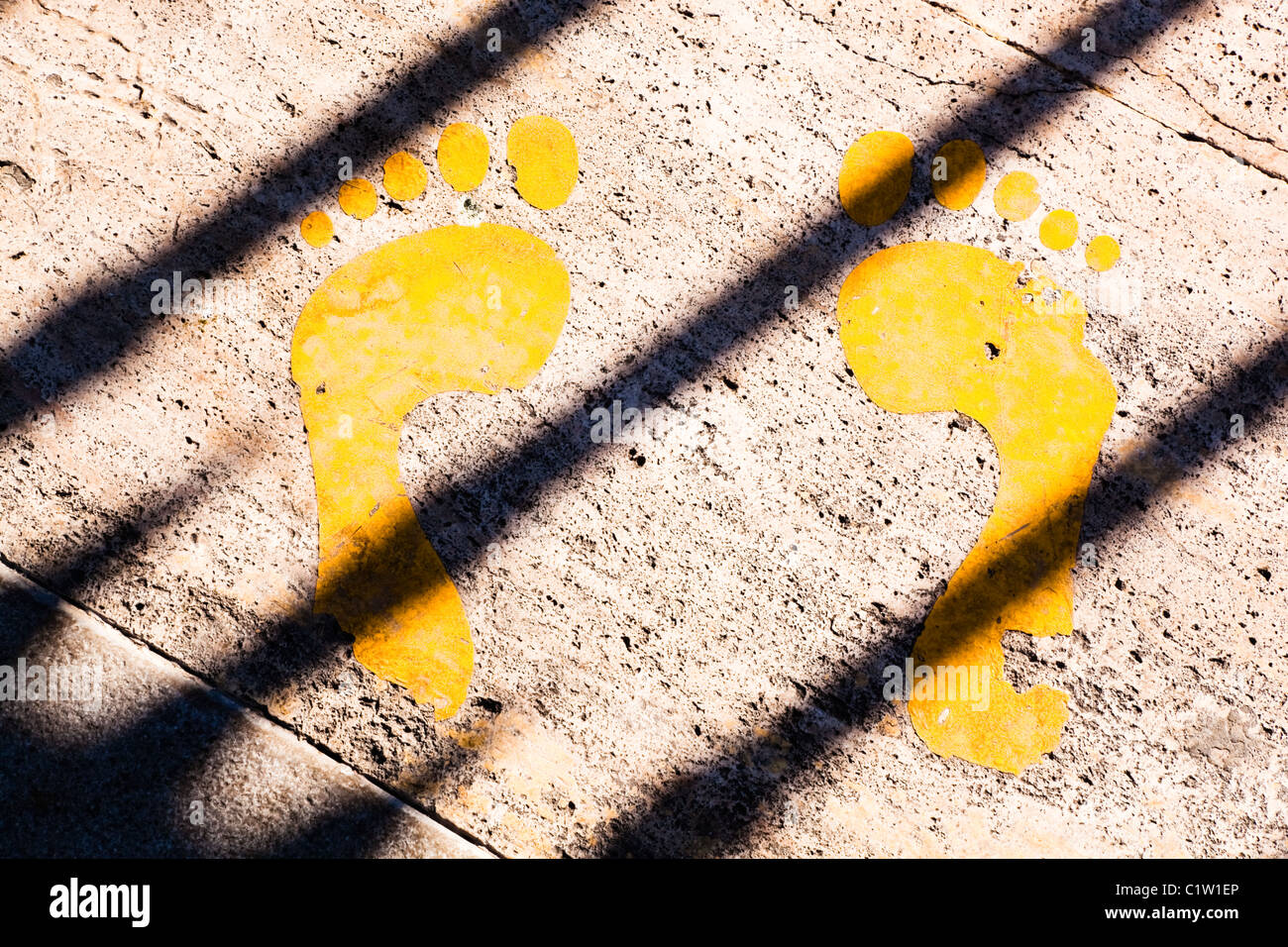 Yellow painted footprints in pavement with shadow of bars across them. - Stock Image