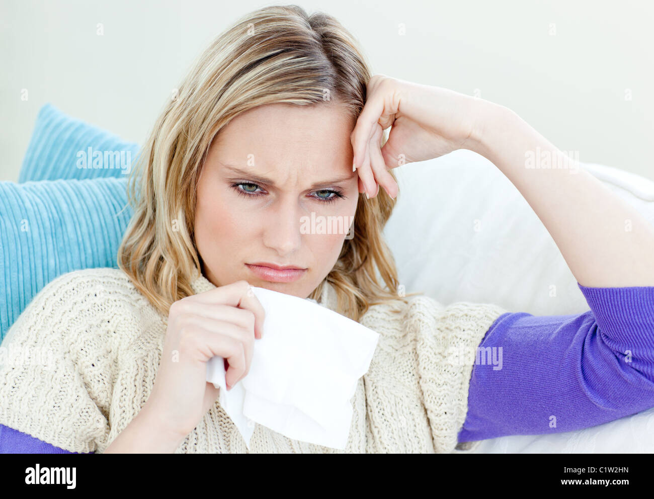 Diseased woman lying on a sofa with tissues - Stock Image