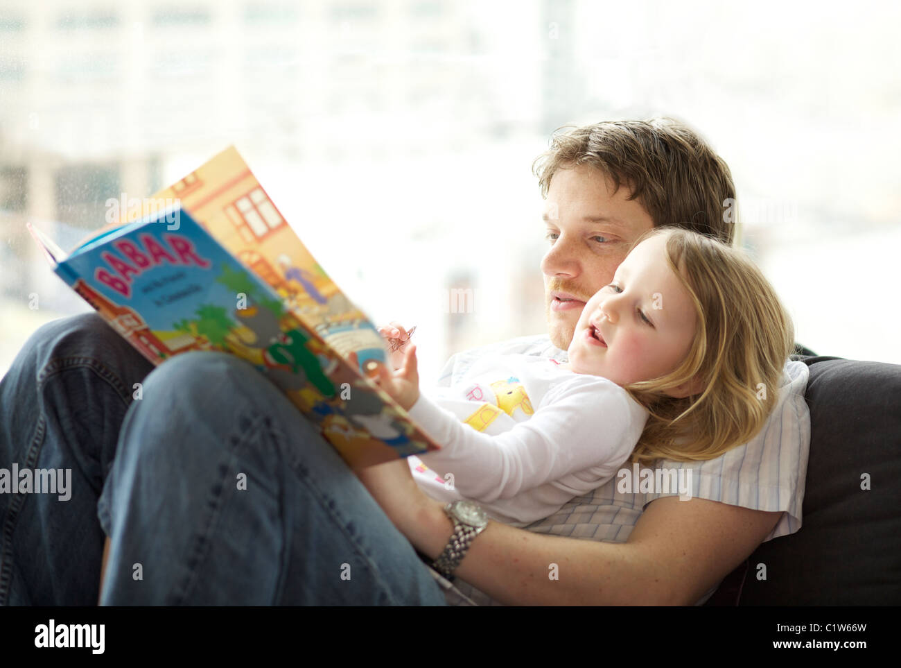Caucasian father reading Babar the Elephant children book to his three year old daughter - Stock Image