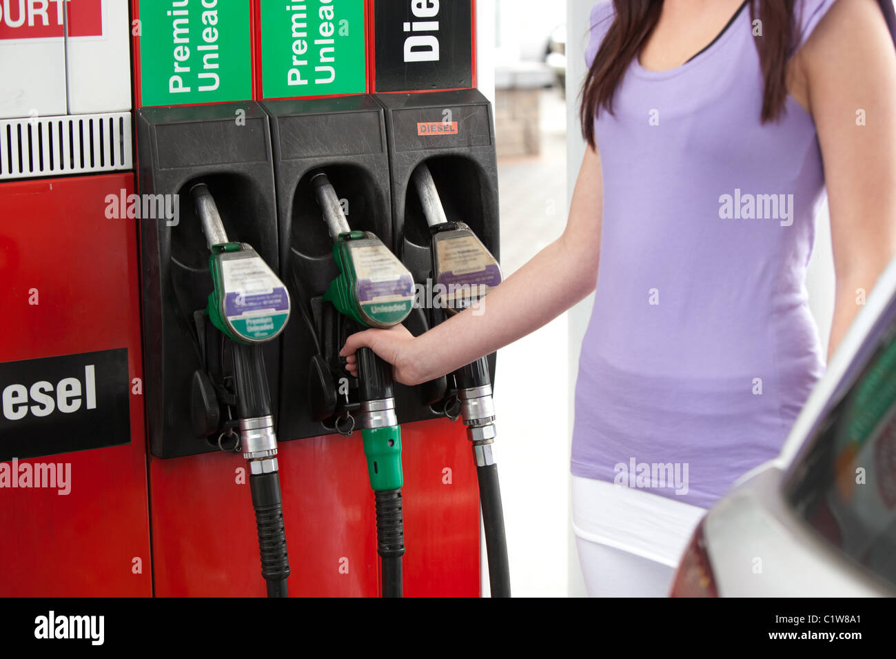 Close-up of a young woman refueling her car - Stock Image