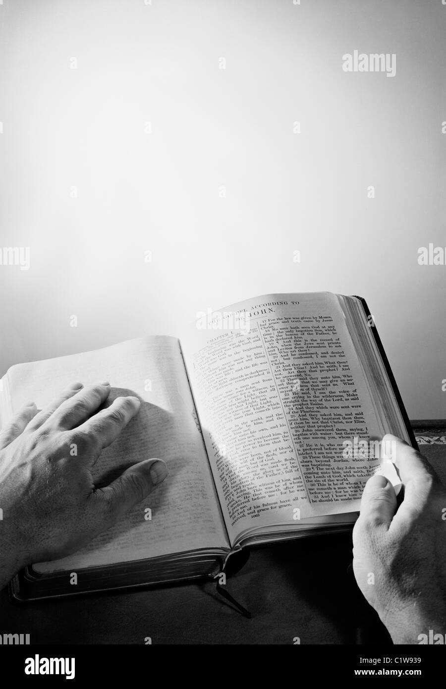Mans hands on bible - Stock Image
