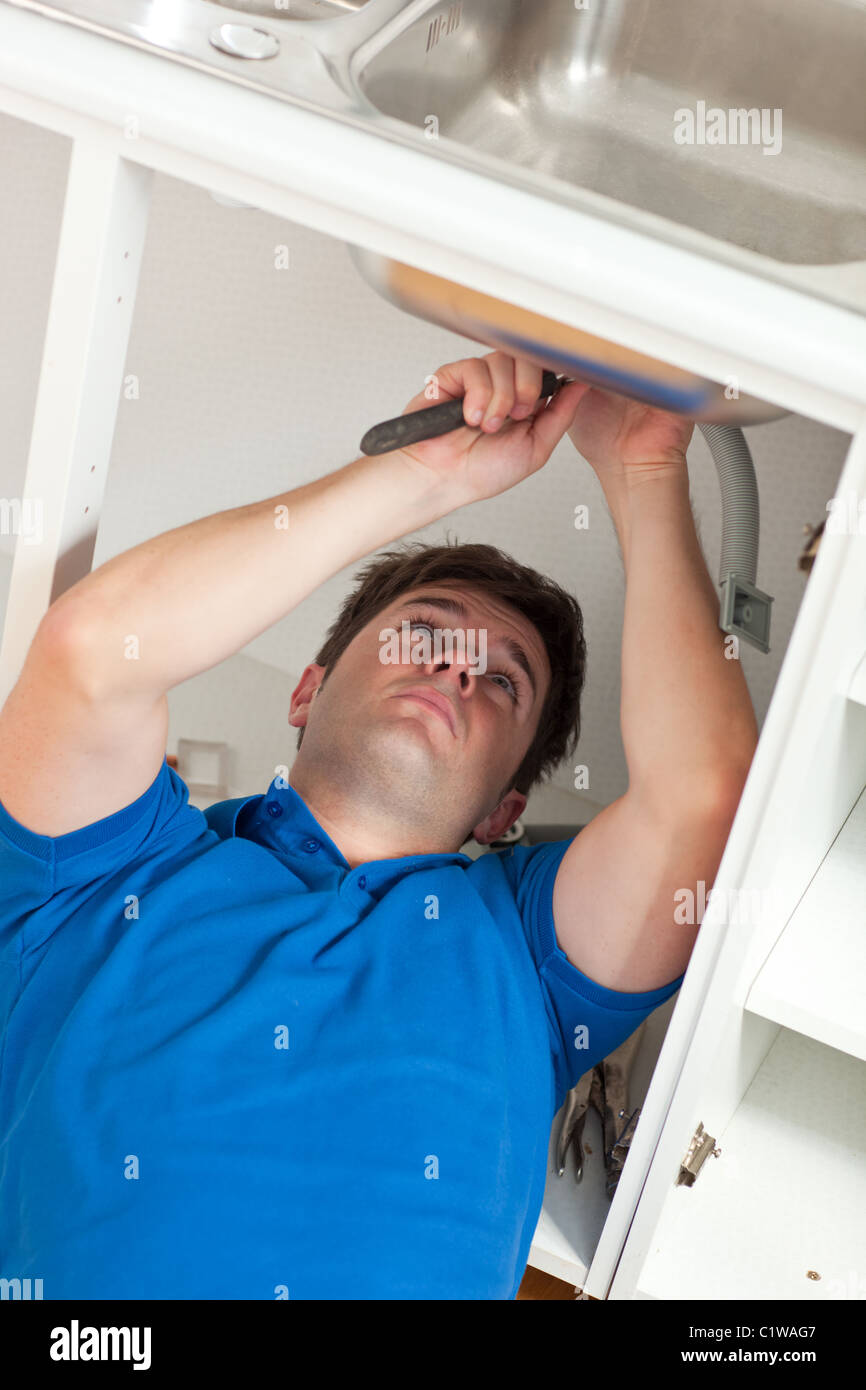 Manual man repairing his sink in the kitchen - Stock Image
