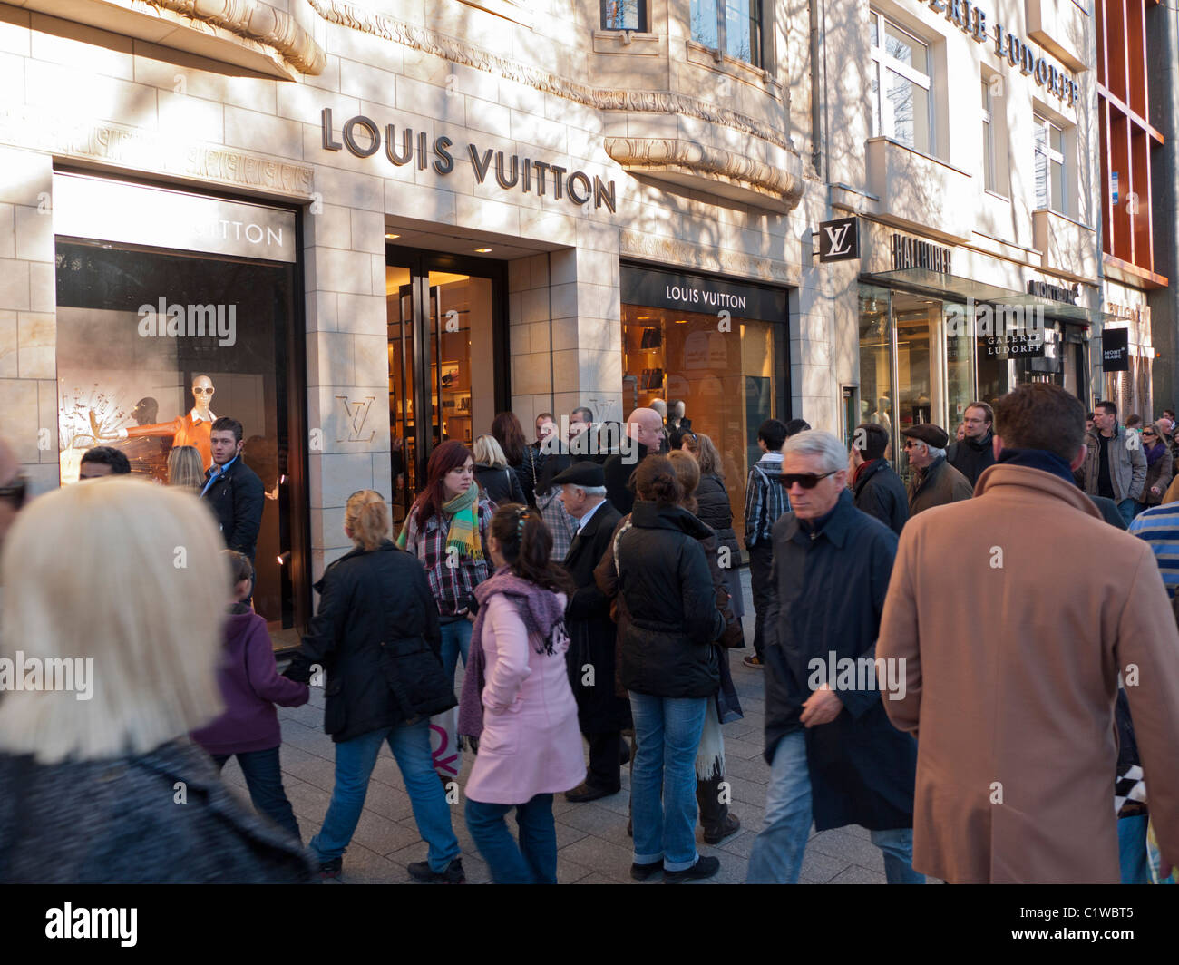 Crowds of shoppers on upmarket shopping street Konigsallee in Dusseldorf in Germany - Stock Image
