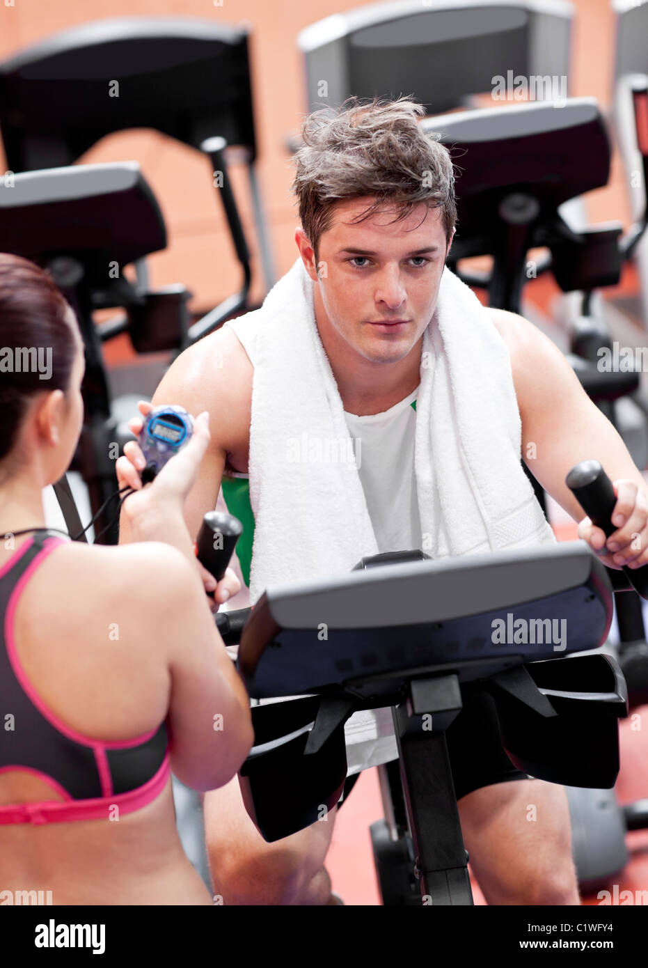 Female coach using a chronometer while man is doing physical exercises in a fitness centre - Stock Image