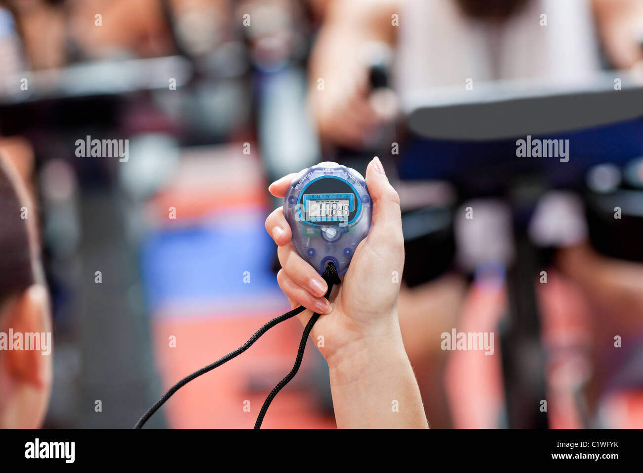 Close-up of a chronometer holding by a female coach in a sport centre - Stock Image