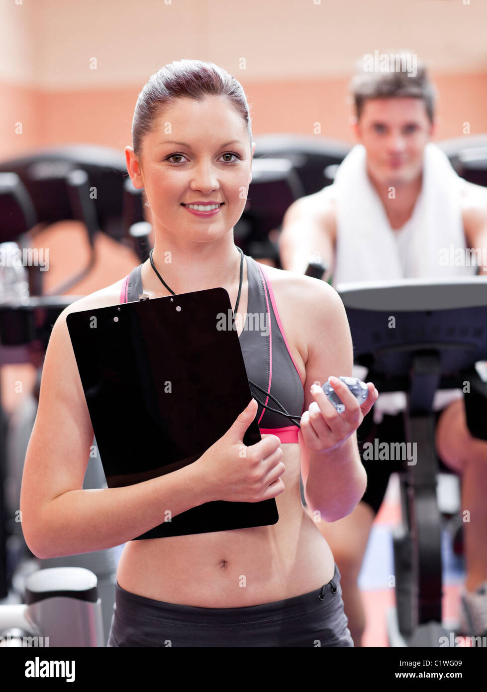Happy coach measuring time with a chronometer while man is doing exercises - Stock Image