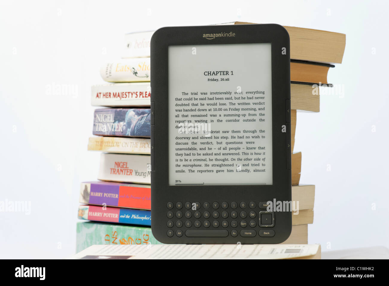 An Amazon Kindle ebook reader and a stack of paperback books on a white background. The Kindle 3 model. FOR EDITORIAL - Stock Image