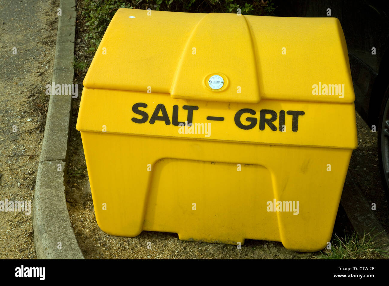 Yellow salt grit container by roadside - Stock Image
