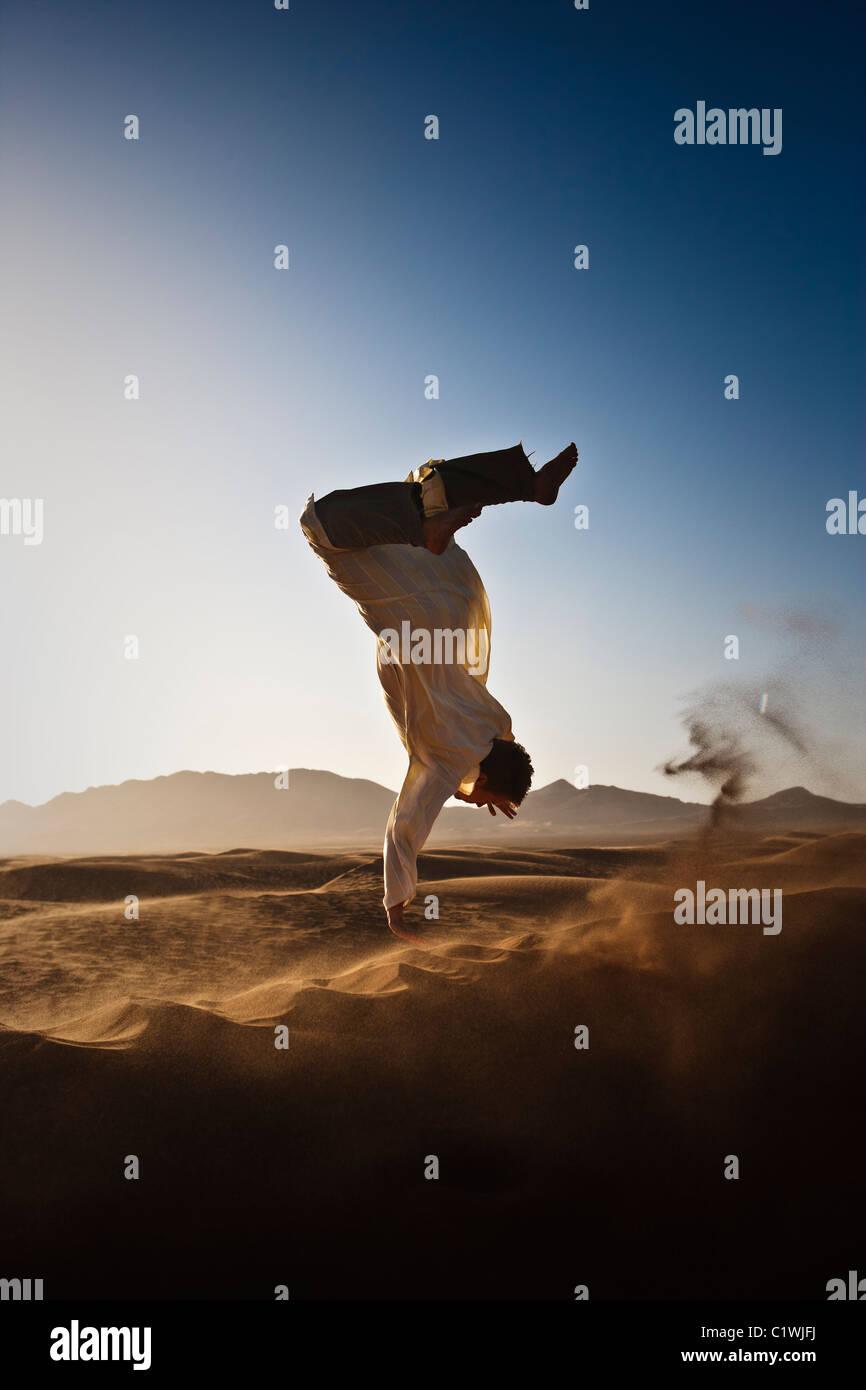 Western man in traditional Berber clothing jumping backflip off sand dune in Sahara Desert, Morocco, Africa - Stock Image