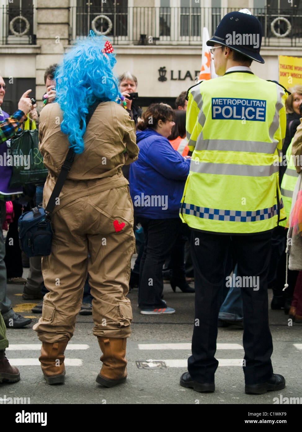 A demonstrator dressed as a clown stands mockingly next to a policeman during protests against Government cuts in - Stock Image