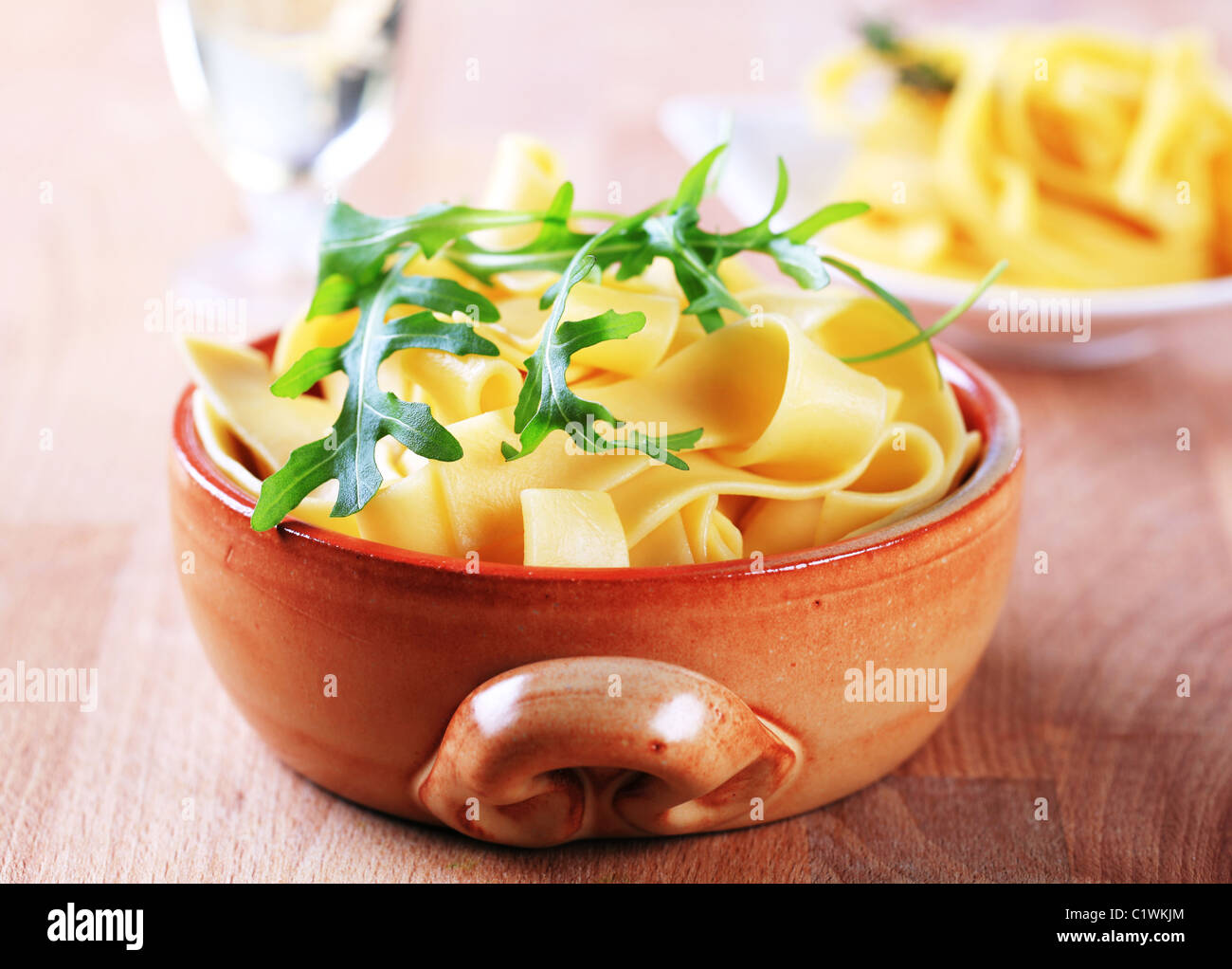 Cooked ribbon pasta in a ceramic pot - Stock Image