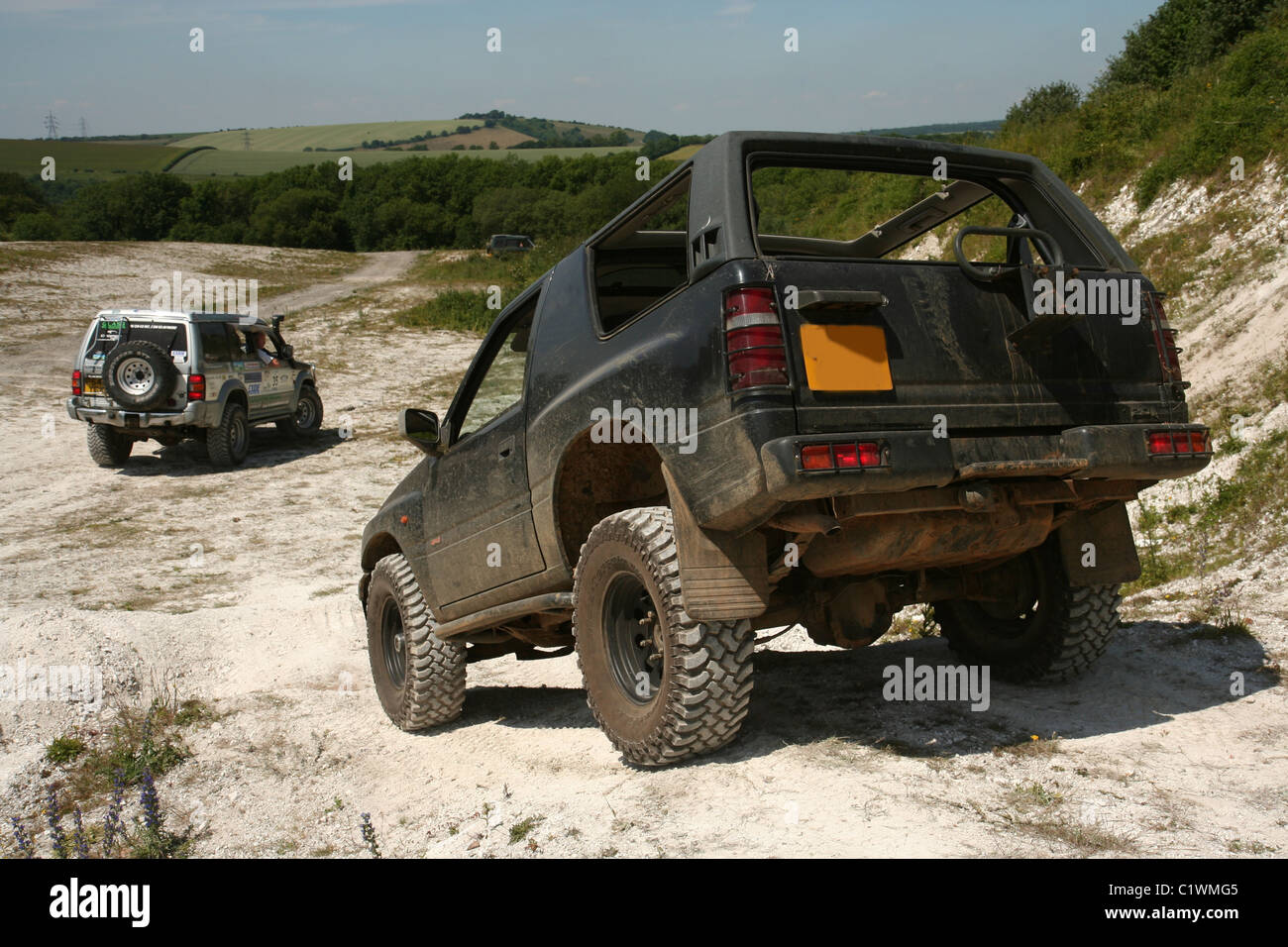 Two 4x4 off road vehicles driving in a chalk pit. Stock Photo