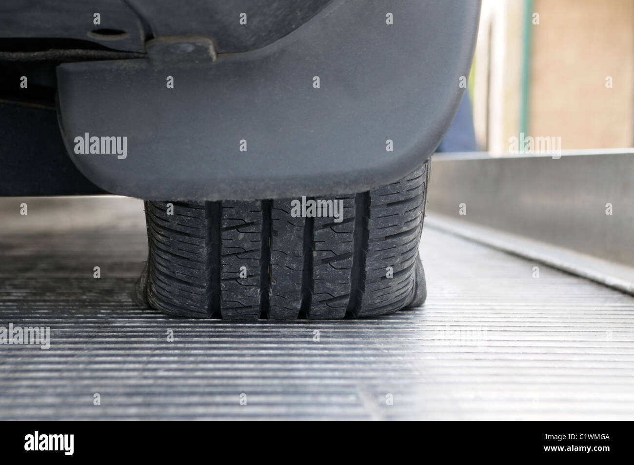 Flat tire on car on top of a flatbed wrecker truck - Stock Image
