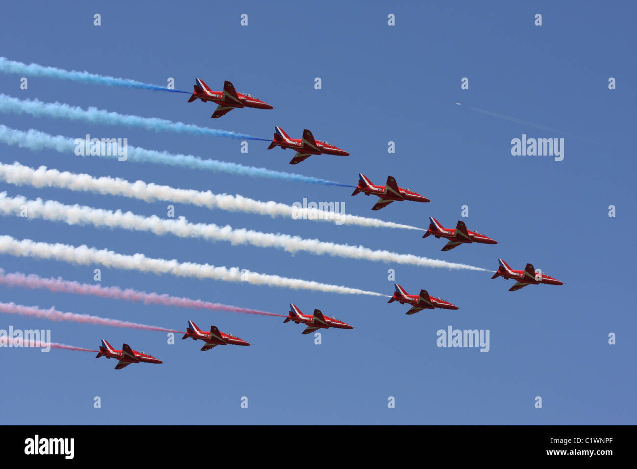 The red arrows flying in formation across a blue sky trailing smoke. - Stock Image