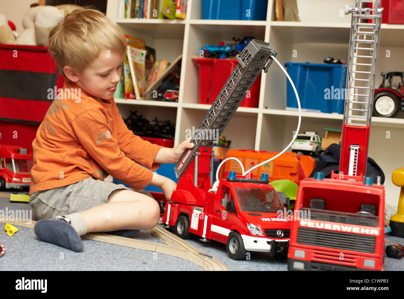 Young Boy Playing With Toy Fire Truck In Children S Room