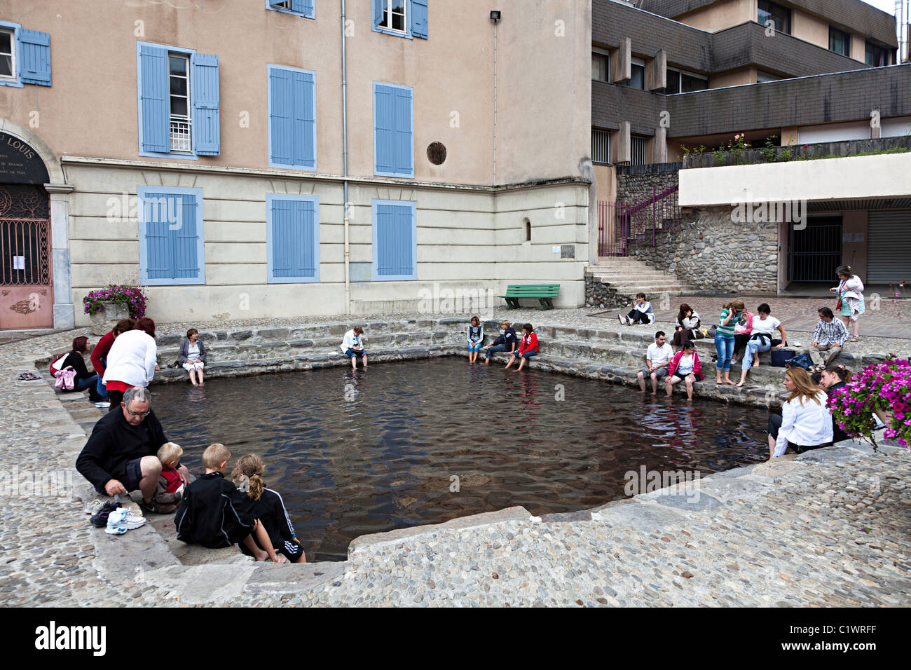 People soaking feet in mineral rich thermal springs in Ax-les-Thermes department Ariege France - Stock Image