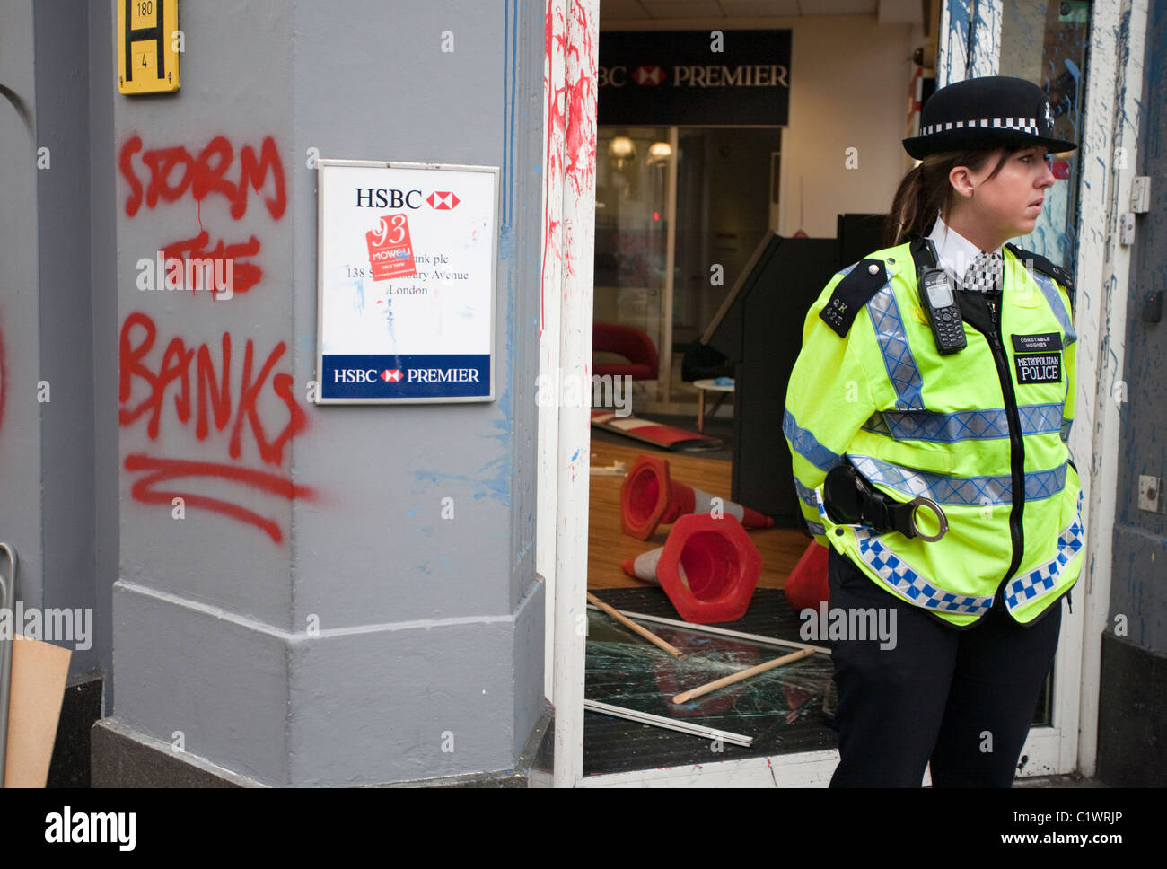Policewoman stands guard at a branch of HSBC Bank on Cambridge Circus shortly after it was ransacked by Anarchists. - Stock Image