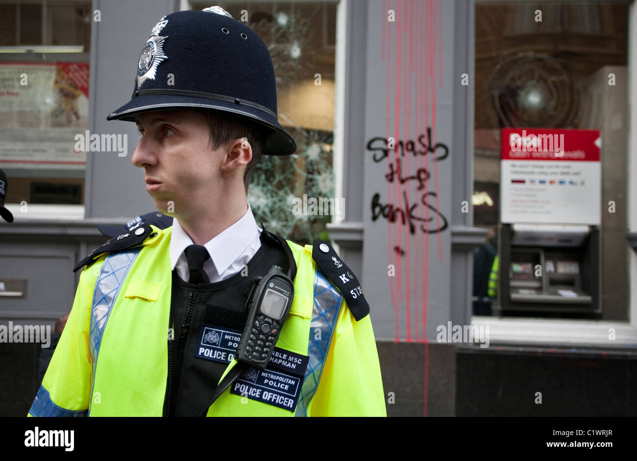 Policeman stands guard at a branch of HSBC Bank on Cambridge Circus shortly after it was ransacked by Anarchists. - Stock Image