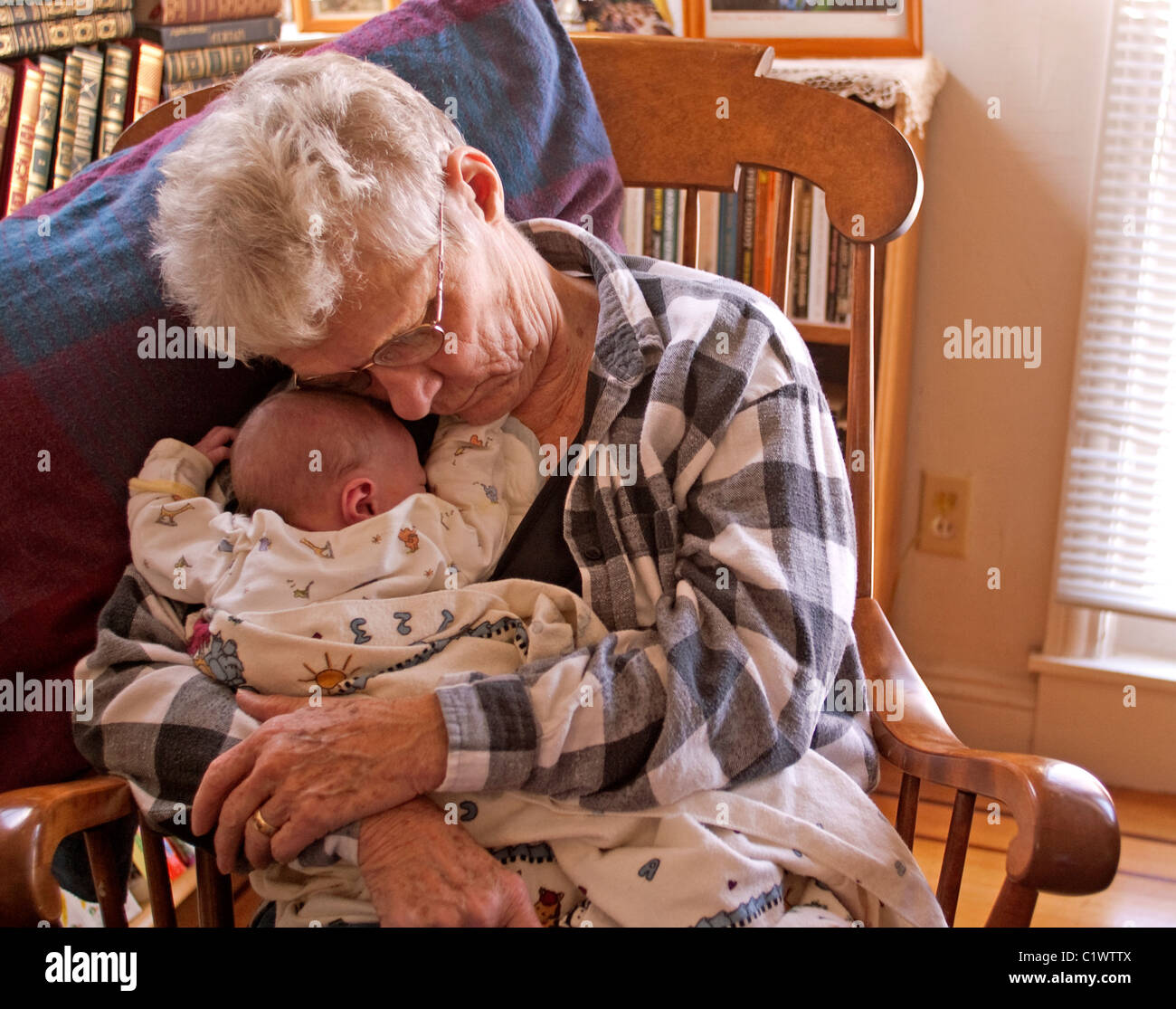 Grandmother napping with her newborn grandson. - Stock Image