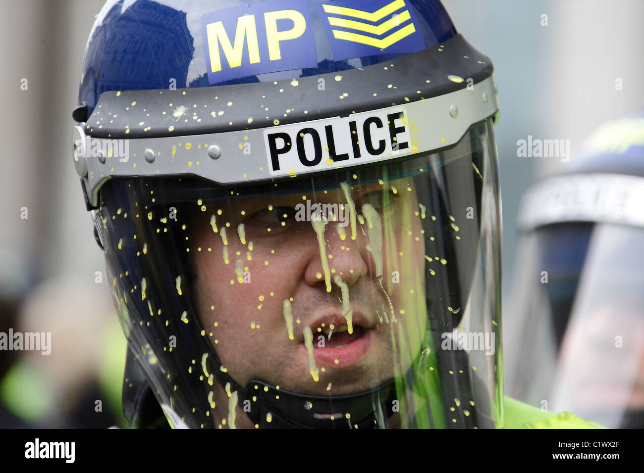 A police Sgt splattered by yellow paint thrown by a protester during 26/03/2011 demo against cuts - Stock Image