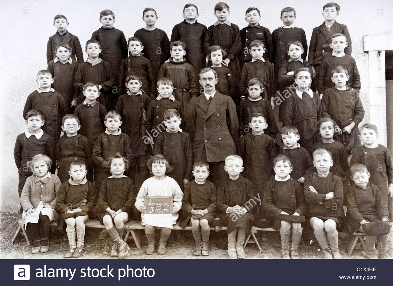 vintage formal group photo of school children with teacher - Stock Image